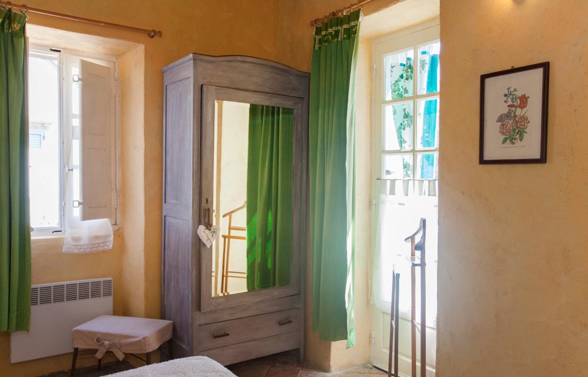 Vacanze in Corsica? Focus sull'armadio della camera Castagno, affiancato da una finestra con tendine a vetro e scuri interni e dalla portafinestra con tendine a mezz'altezza, entrambe dotate di tendoni oscuranti verdi.