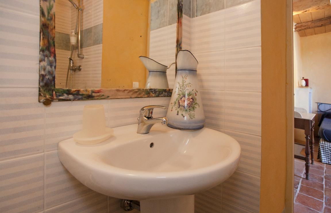 Corsica affitti vacanze: dettaglio del bagno della camera Ulivo, in primo piano il lavabo con una caraffa per abluzioni vintage in metallo laccato bianco con motivo floreale. Un grande specchio rettangolare con cornice artigianale in tessuto fantasia. A destra si scorge parte della camera, con un particolare dello scrittoio dal ripiano in marmo.