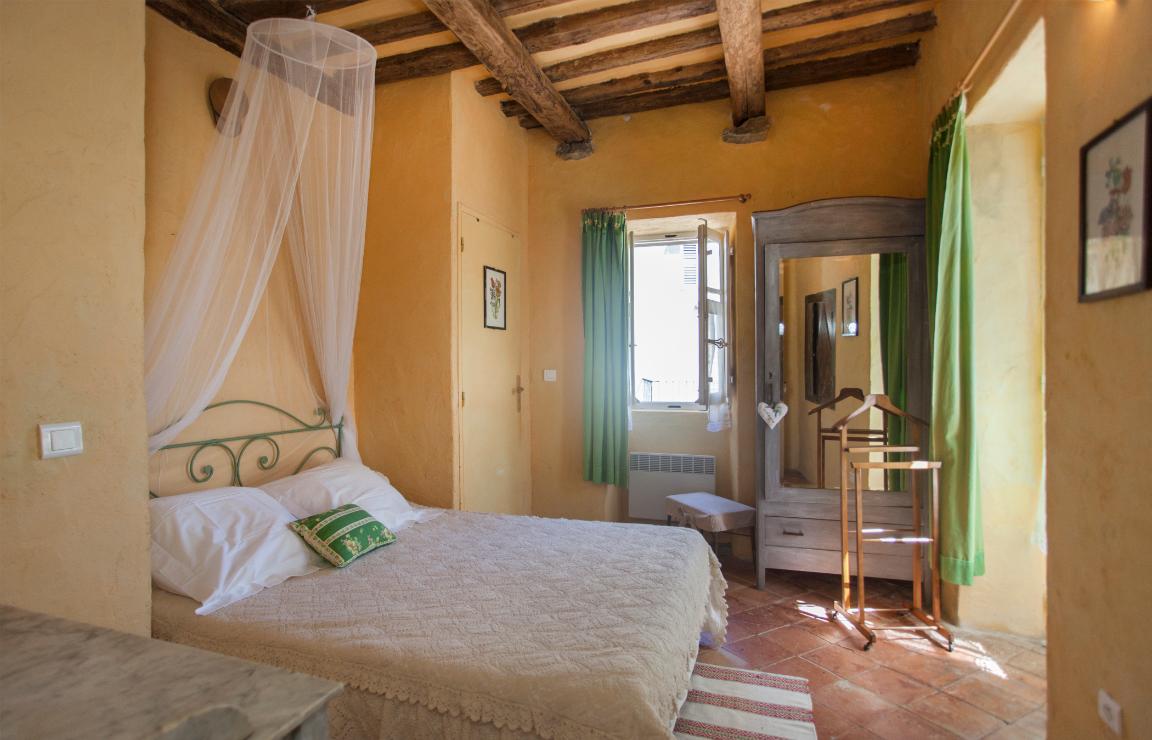 Panoramica della camera Castagno, al centro l'ampio letto matrimoniale con baldacchino di velo, sulla parete laterale si apre una finestra, al suo fianco un armadio a specchio. Sulla parete frontale al letto si intravede la portafinestra.