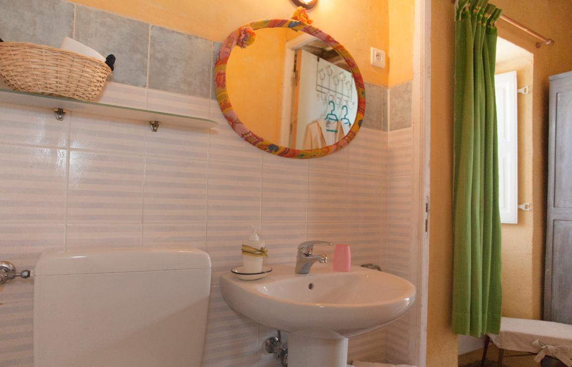 Vacanze in Corsica? Focus sulla zona lavabo del bagno della camera Castagno, con mensola in vetro sulla sinistra e insolito specchio ovale provvisto di cornice artigianale in stoffa fantasia sui toni del giallo, rosa e arancio.