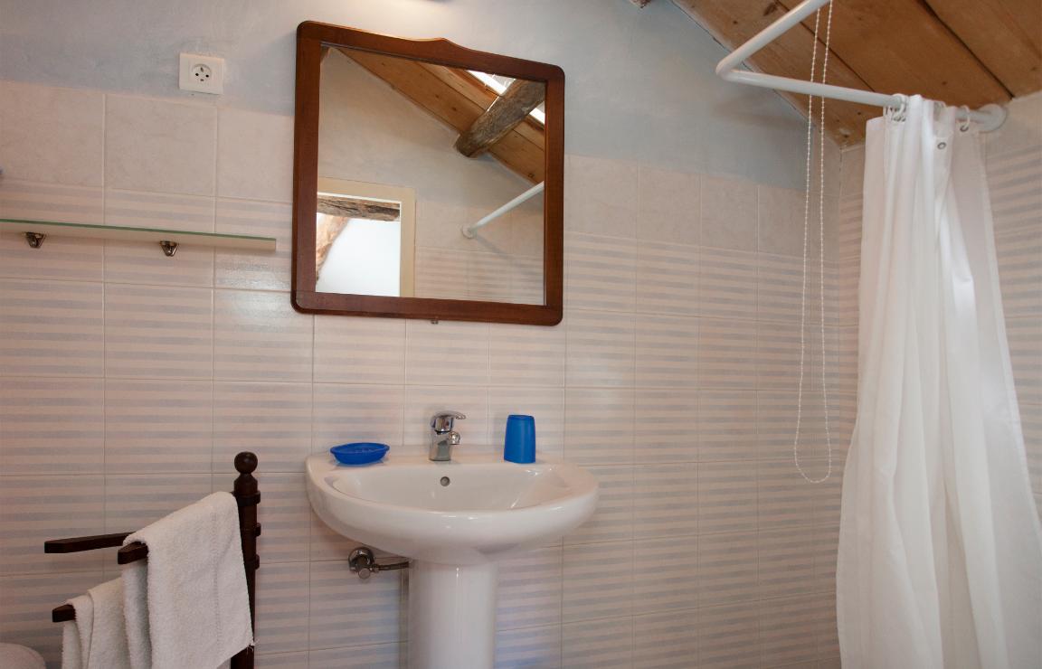 Dormire in Corsica? Focus sul bagno della camera Mirto. A destra si osserva un particolare della doccia, quindi la zona lavabo con un grande specchio rettangolare a cornice lignea, affiancato da una mensola in vetro. A sinistra del lavandino si trova un portasciugamani a bracci mobili in legno. Piastrelle con motivo a righe bianche e azzurre coprono le pareti.