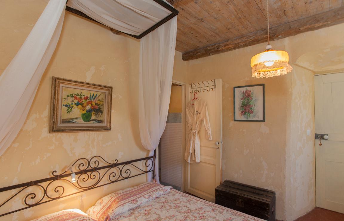 Focus sulla camera Corbezzolo: si apprezza il soffitto a listoni di legno, da cui pende un lampadario impreziosito da pizzi. Sulle pareti si trovano due dipinti di soggetto floreale, il più grande dei quali sormonta il letto doppio a baldacchino di velo. Si intravede l'ingresso del bagno privato.