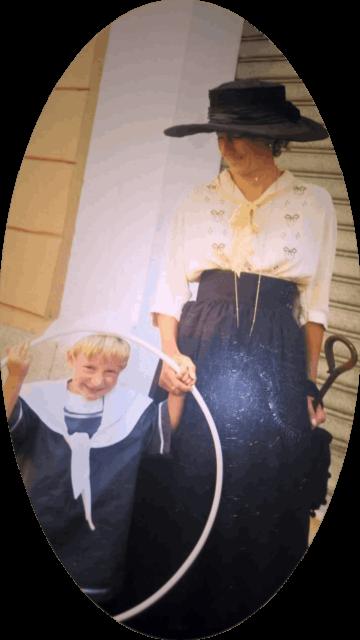 B&B Corsica - Luciana Masinari, la padrona di casa, in abbigliamento ottocentesco, gonna blu, camicetta beige ricamata e ampio cappello blu, in compagnia del giovane figlio vestito alla marinara.
