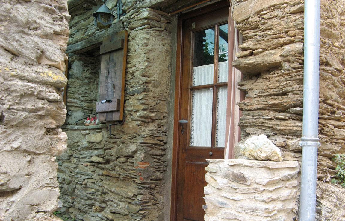 Case affitto Corsica: focus sull'ingresso della Casetta Pergola, incastonato tra spessi muri formati da sottili strati di pietre. La porta è in legno scuro e vetro, con una tendina bianca all'interno e una tenda oscurante all'esterno. A sinistra della porta si apre una finestra protetta da persiane di legno, sormontata da una piccola lampada in ferro battuto.